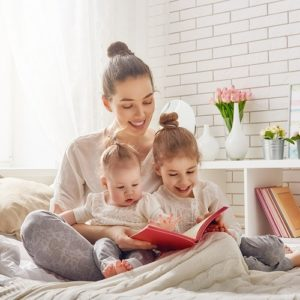 Young mother reading a book to her children.
