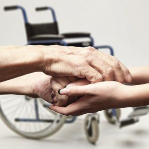 Hands of an elderly man holding the hand of a younger woman in front of a wheel chair.