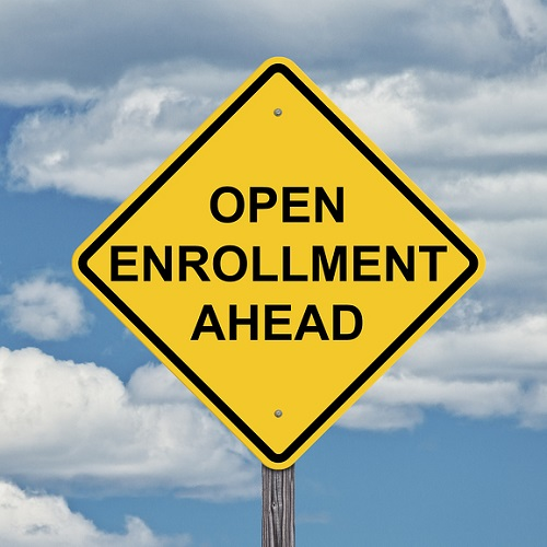 Yellow sign with open enrollment for health care.