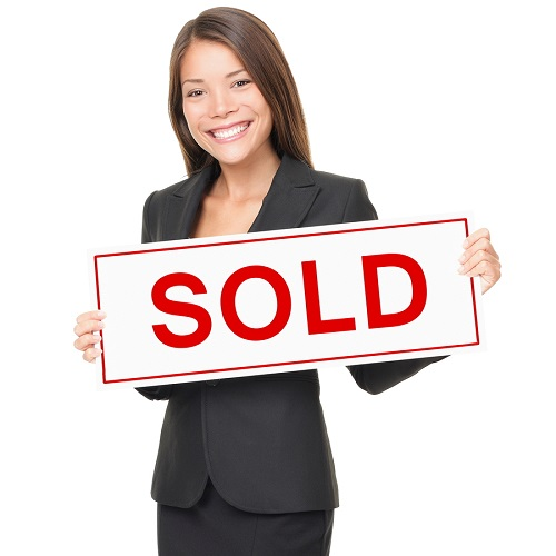 Real estate agent holding sold sign isolated on white background.
