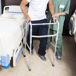 Nurse Helping Patient In Using Walker